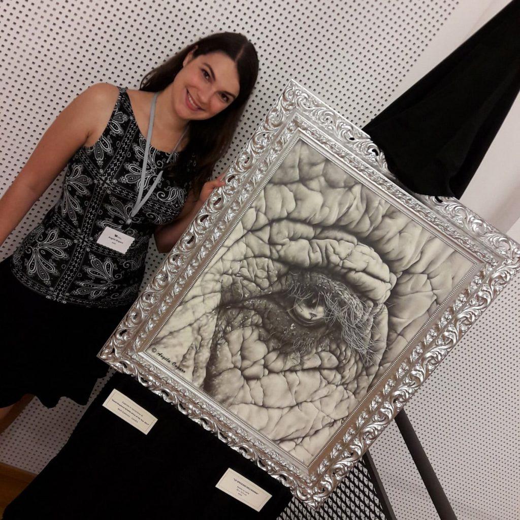 L'artista Angela Ongaro con il suo disegno a matita Lo specchio dell'anima che rappresenta un occhio di elefante